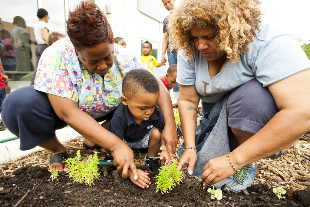 photo of young child and two teachers tending growing plants