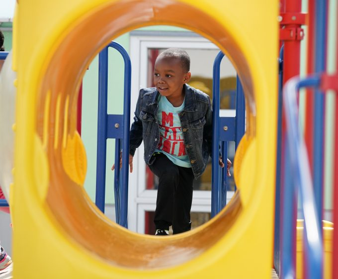 photo of young child outside playing on playground equipment