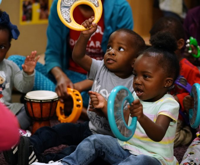 photo of young children playing musical instruments