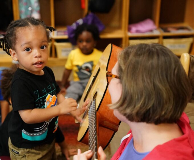 photo of woman holding a guitar while a young child strums the strings
