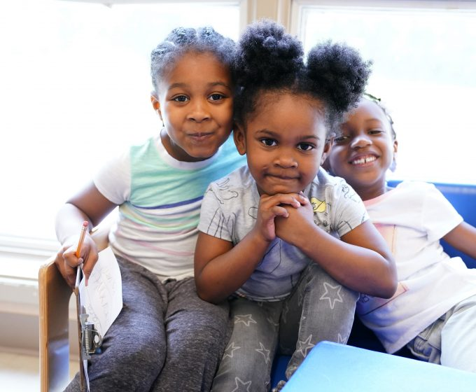 photo of three young girls sitting together